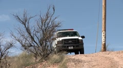 A border patrol vehicle is parked on a dirt road. Stock Footage