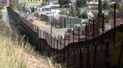 A hillside view front behind a large fence looking down on an intercity street Stock Footage