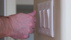 A man turns a light switch on and off Stock Footage