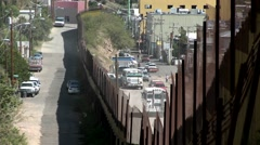 A border fence shows the separation of a community between a rural area and a Stock Footage