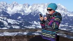 Attractive woman texting with her phone in the mountains HD Stock Footage
