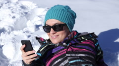 Happy girl lying in deep snow and texting with her phone HD Stock Footage