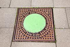 A manhole cover in the street to enter the canalisation - stock photo