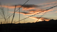 The sun sets over an area protected by barbed wire. - stock footage