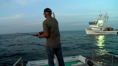 A man fishes from the back of a small boat. Stock Footage