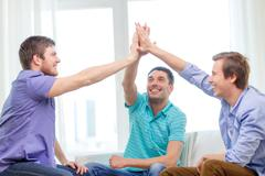 Smiling male friends giving high five at home Stock Photos