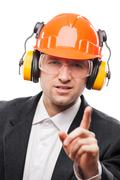 Businessman in safety hardhat helmet gesturing exclamation point finger sign - stock photo