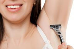 Beauty toothy smiling young woman hand holding razor sharp blade shaving armp Stock Photos