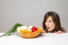 Stock Photo of woman with green vegan food. surprise emotion.
