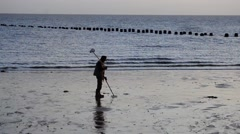 A Man Looks for Metal with a Metal Detector on the Beach Stock Footage