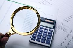 Man considers the budget through a magnifying glass Stock Photos