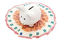 Stock Photo of Piggy bank surrounded by ten Euros notes