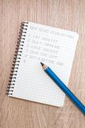 Blue pencil and notepad with resolutions Stock Photos