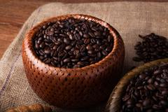 Roasted coffee beans in a bamboo basket Stock Photos