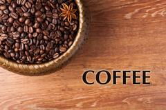 roasted coffee beans in a bamboo basket with title - stock photo