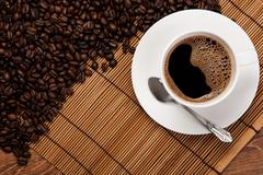 cup of black coffee with roasted coffe beans - stock photo