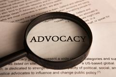 document with the title of advocacy under a magnifying glass - stock photo
