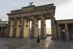 Cyclist approaches the Brandenburg Gate in the early morning, Historic Mitte, Stock Photos