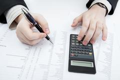 businessman holding a pen and counts the budget - stock photo