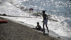 Children play game on beach, girl play football at seaside, silhouette Arkistovideo