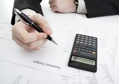 Stock Photo of businessman holding a pen and counts the budget