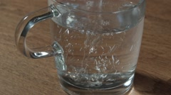Close up of pouring hot water  in transparent glass cup and inserting a tea bag Stock Footage