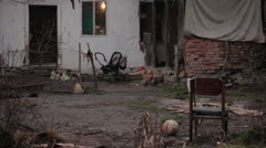 Ruined old house made of mud with old children's staff in the yard, tilt up. Stock Footage