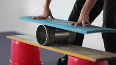 A man balances on a board set on top of a roller. Stock Footage