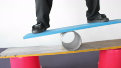 A man balances on a board and a tube. Stock Footage