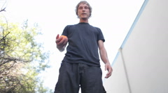 A man does tricks juggling one ball with his feet. - stock footage
