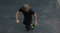 A man does a juggling act in the street with three colored balls. - stock footage