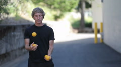 A man does a juggling act with four orange balls. - stock footage