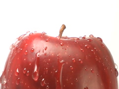 Water drips down side of rotating red apple - stock footage