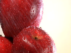 Pull back from water showering on stack of rotating red apples Stock Footage
