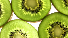 Full frame slices of kiwis rotate through frame Stock Footage