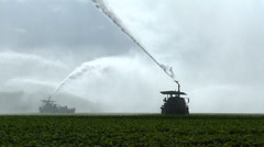 Irrigation trucks spraying water on field, south Florida cash crops Stock Footage