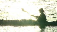 Sun reflects off water, kayaker paddles through frame Stock Footage