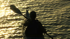 Kayaker paddles away from as sunset reflects off water - stock footage