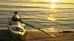 Kayak on shore, water ripples in the sunset - stock footage