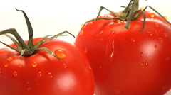 Water trickles off two red tomatoes Stock Footage