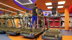 A young man running on a treadmill in a gym - stock footage