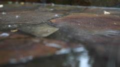Rain falls on a stone sidewalk. Stock Footage
