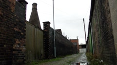 Old industrial bottle kiln building cobbled alley industrial scene Stock Footage