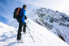 Winter vacation: mountaineer takes a rest looking at the mountain panorama - stock photo