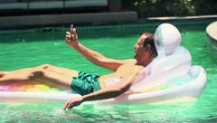 Man taking selfie photo with cellphone lying on air mattress in swimming pool HD Stock Footage