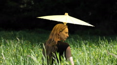 A young woman with an umbrella standing in tall grass. Stock Footage