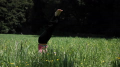 A woman doing yoga in a field falls over from her head stand. Stock Footage