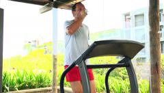Stock Video Footage of Young man running on treadmill and drinking water in gym HD