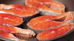 Close-up of salmon steaks are fried in a pan Stock Footage