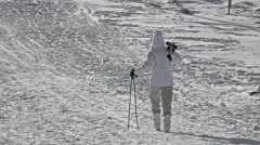Young girl climb the mountain ski slope for skiing down Stock Footage